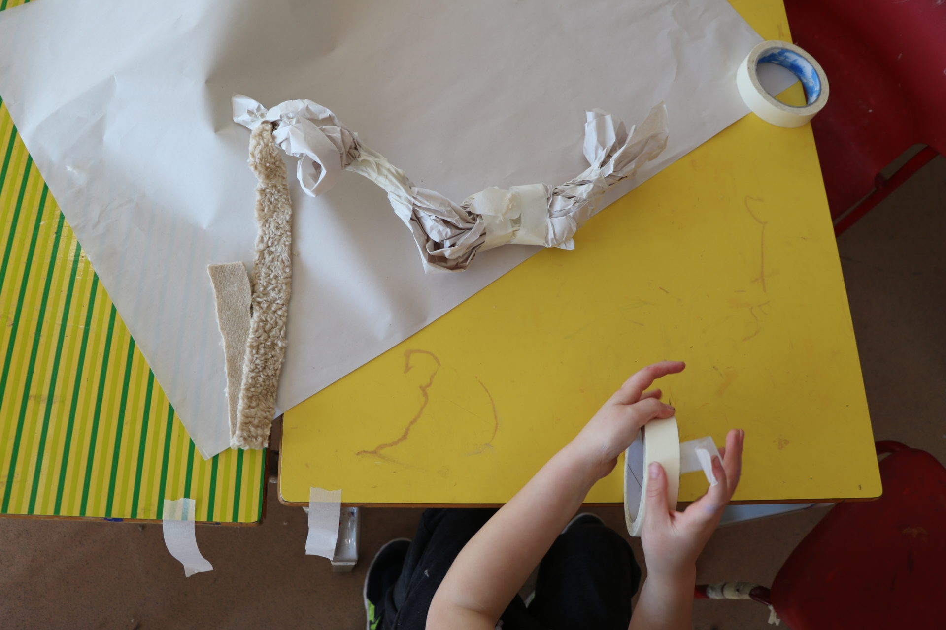 Hands, paper, yellow table
