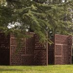 Large terracotta panels situated in a green landscape